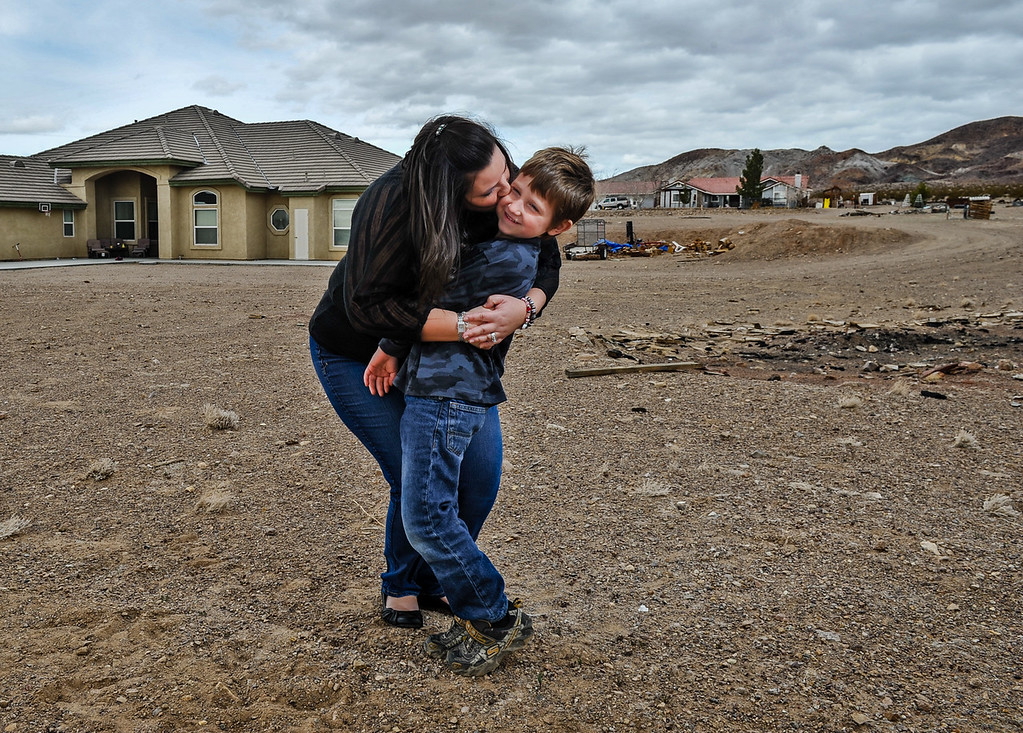 Description of . Reanna Banks, 33, hugs her son Aiden, 6, in the front yard of their family's 10-acre land parcel in Hinkley, Calif. on Thursday, March 7, 2013. Banks has been a dovoted resident for most of her adult life, and her son is a third generation Hinkley resident. (Rachel Luna / San Bernardino Sun)
