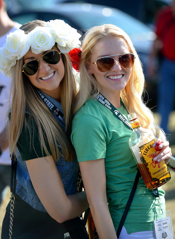 Description of . Michigan State alumni Erin Savage, left, and Hannah Hoppough get ready for the Rose Bowl game, Wednesday, January 1, 2014. (Photo by Michael Owen Baker/L.A. Daily News)