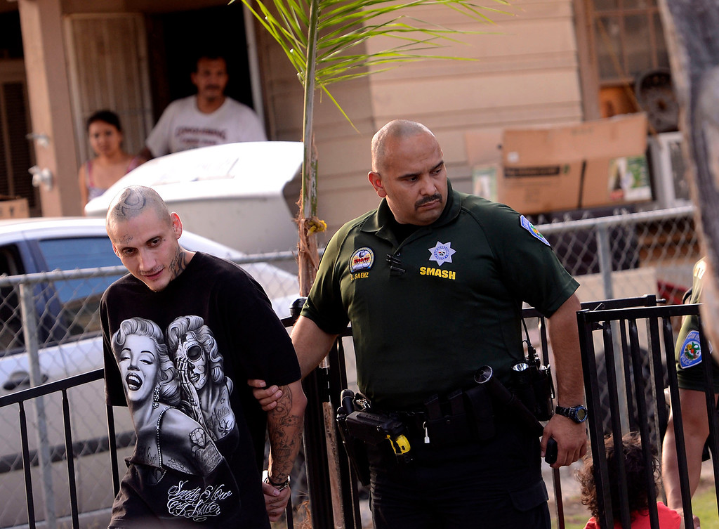 Description of . San Bernardino Police officer Serbando Saenz arrests a man for parole violations along the 200 block of Tenth Street as seen during a county wide police sweep in San Bernardino August 2, 2013. GABRIEL LUIS ACOSTA/STAFF PHOTOGRAPHER.