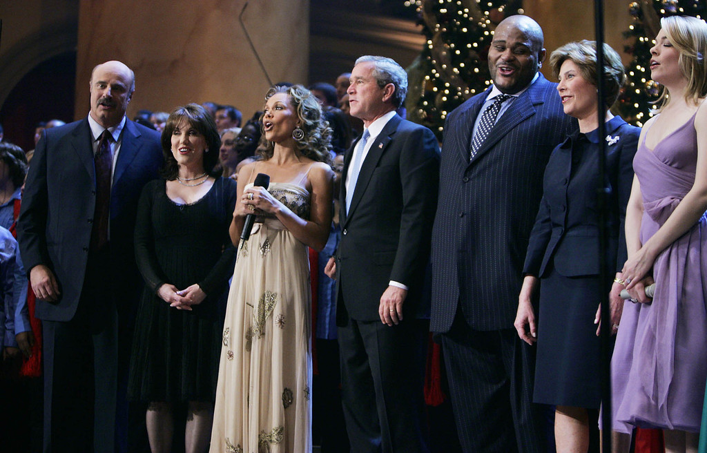 Description of . President and first lady Laura Bush join host Dr. Phil, left, and Robin McGraw, second left, and performers Vanessa Williams, third left, Ruben Studdard, third right, and LeAnn Rimes, right, during taping of the annual Christmas in Washington concert, at the National Building Museum, Sunday, Dec. 12, 2004, in Washington.   (AP Photo/Manuel Balce Ceneta)
