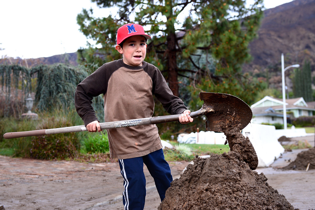 Description of . Max Loera, 9, helps clean up mud at Trish Emery's home on Rainbow Drive in Glendora Saturday, March 1, 2014. The neighborhood sits below the Colby Fire burn area. (Photo by Sarah Reingewirtz/Pasadena Star-News)