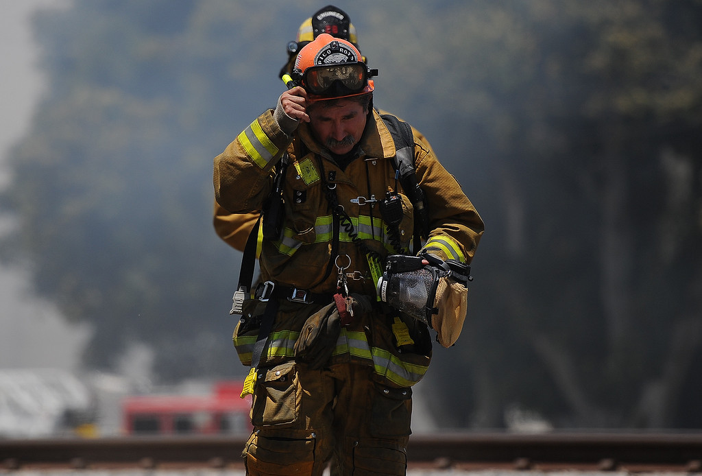 Description of . Los Angeles County firefighter capt. takes a break after battling a 3-alarm fire at an abandoned warehouse near 9th Avenue and Clark Avenue on Tuesday, July 9, 2013 in City of Industry, Calif.  (Keith Birmingham/Pasadena Star-News)