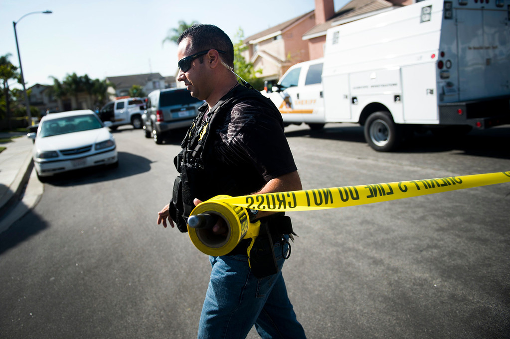 Description of . Sgt. Jesse Dengas puts up a crime scene tape at the scene of a deputy-involved shooting at the 5400 block of Brushwood Court in Chino Hills on Friday, March 28, 2014. (Photo by Watchara Phomicinda/ San Gabriel Valley Tribune)