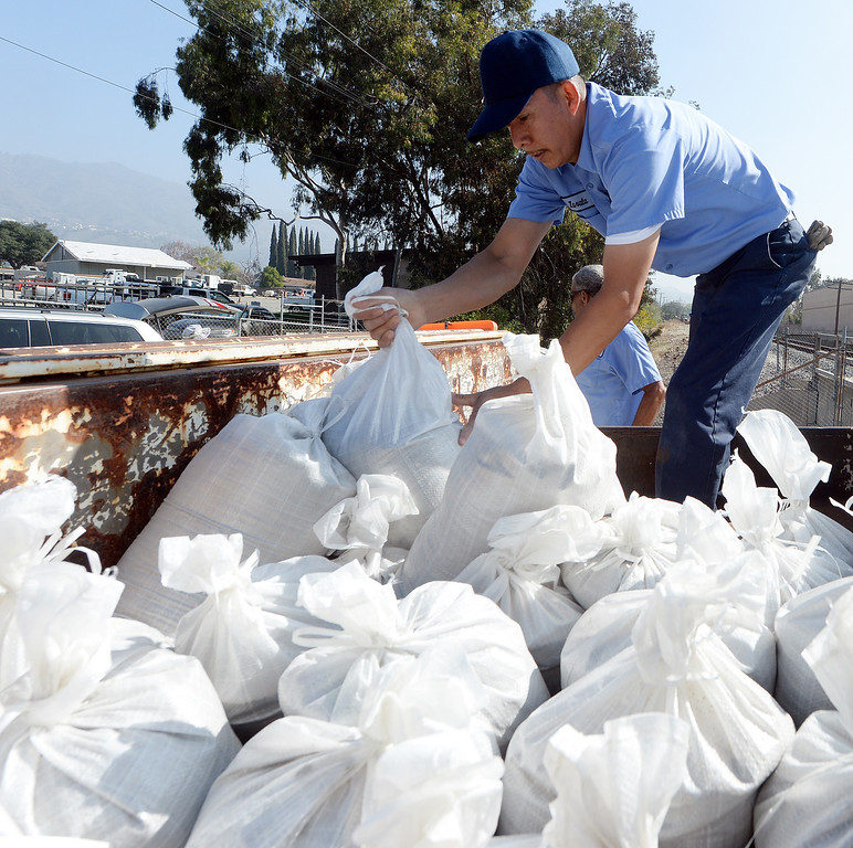 Description of . St. Lucy's Priory High School employees Enrique Zavala loads sand bags into a truck at the Glendora city yard Tuesday February 25, 2014. Possible heavy rains in the coming days could create mud flows off of the burned hill sides caused by January's Colby Fire. (Will Lester/Inland Valley Daily Bulletin)