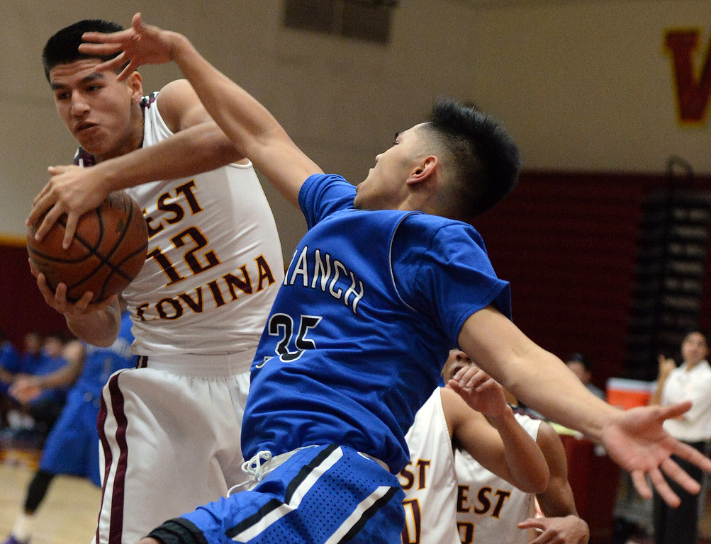 Description of . West Covina's Jacob Acosta (12) rebounds past Diamond Ranch's Paolo Reorizo (35) in the first half of a prep basketball game at West Covina High School in West Covina, Calif., on Wednesday, Jan. 8, 2014. (Keith Birmingham Pasadena Star-News)