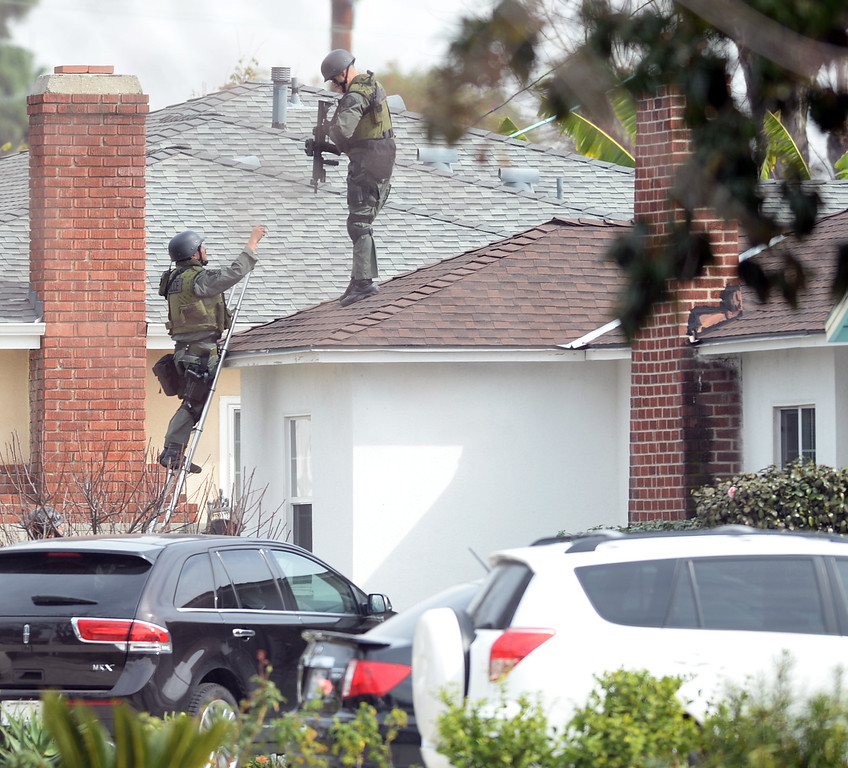Description of . El Monte SWAT Team members enter the home on the 11400-block of Elmcrest Street in El Monte finding the suspect dead after a standoff on Friday March 7, 2014. The suspect shot his neighbor over a dispute Friday morning. (Photo by Keith Durflinger/San Gabriel Valley Tribune)