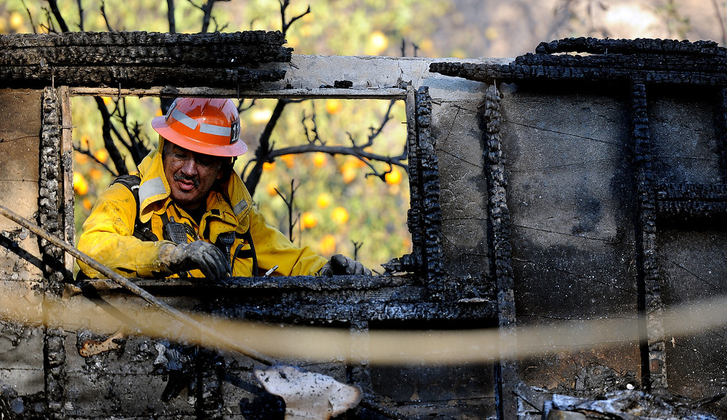 Description of . A Los Angeles County fire capt. out of San Dimas looks through a burned out window at the Singer Estate Kregmont Dr. during the Colby Fire, a 1,700-acre plus brush fire that ignited in the Angeles National Forest north of Glendora  threatening homes and prompting mandatory evacuations in Glendora, Calif., on Thursday, Jan. 16, 2014. (Keith Birmingham Pasadena Star-News)