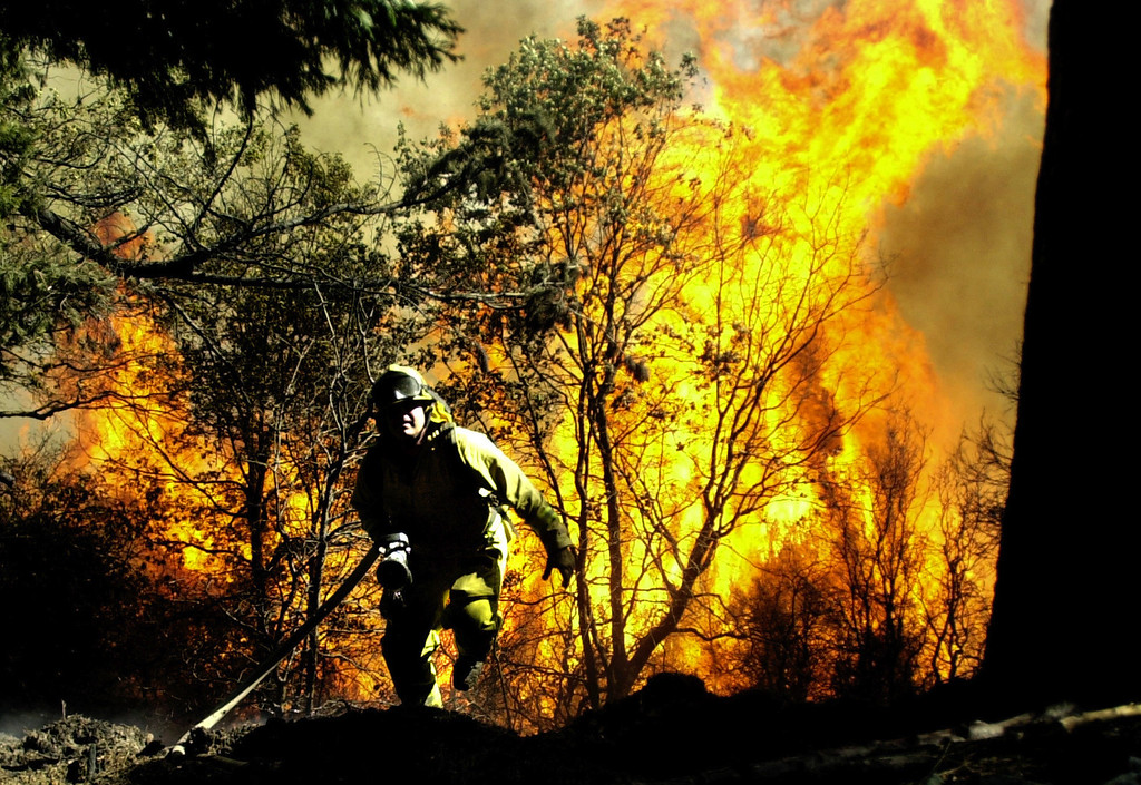 Description of . Ten years ago this month the arson caused Old Fire, fanned by Santa Ana winds burned thousands of acres, destroyed hundreds of homes and caused six deaths. The fire burned homes in San Bernardino, Highland, Cedar Glen, Crestline, Running Springs and Lake Arrowhead and forced the evacuation of thousand of residents. A fire fighter runs up a hill trying to escape a blaze over running a hillside near Crestline, on Sunday October 26, 2003 during the Old Fire. (Staff file photo/The Sun)