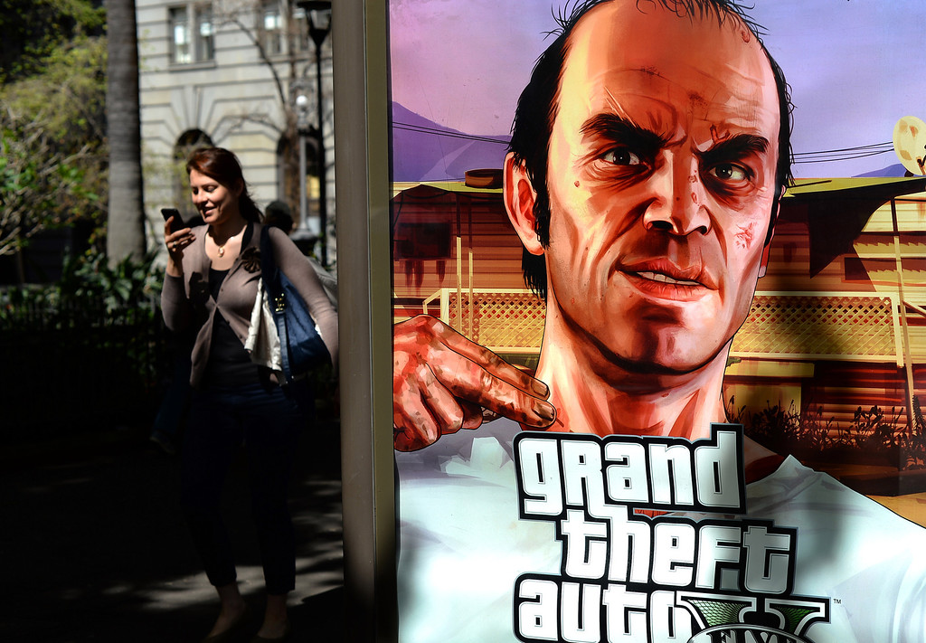 Description of . A woman walks past a billboard advertising the launch of console game Grand Theft Auto 5 in the central business district of Sydney on September 17, 2013. At midnight the doors of select games stores were opened for the launch of the much-awaited Grand Theft Auto 5 game in Australia.         (SAEED KHAN/AFP/Getty Images)