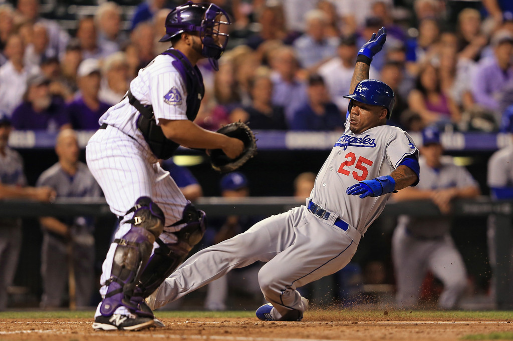 Description of . Carl Crawford #25 of the Los Angeles Dodgers slides home to score behind catcher Wilin Rosario #20 of the Colorado Rockies on a sacrifice fly by Adrian Gonzalez #23 of the Los Angeles Dodgers to give the Dodgers a 4-0 lead in the fifth inning at Coors Field on September 3, 2013 in Denver, Colorado.  (Photo by Doug Pensinger/Getty Images)
