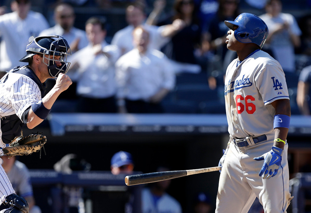 Description of . New York Yankees catcher Chris Stewart, left, pumps his fist after Los Angeles Dodgers' Yasiel Puig, right, struck out looking for the final out in the Yankees 6-4 victory in the first baseball game of a doubleheader on Wednesday, June 19, 2013, in New York. (AP Photo/Kathy Willens)