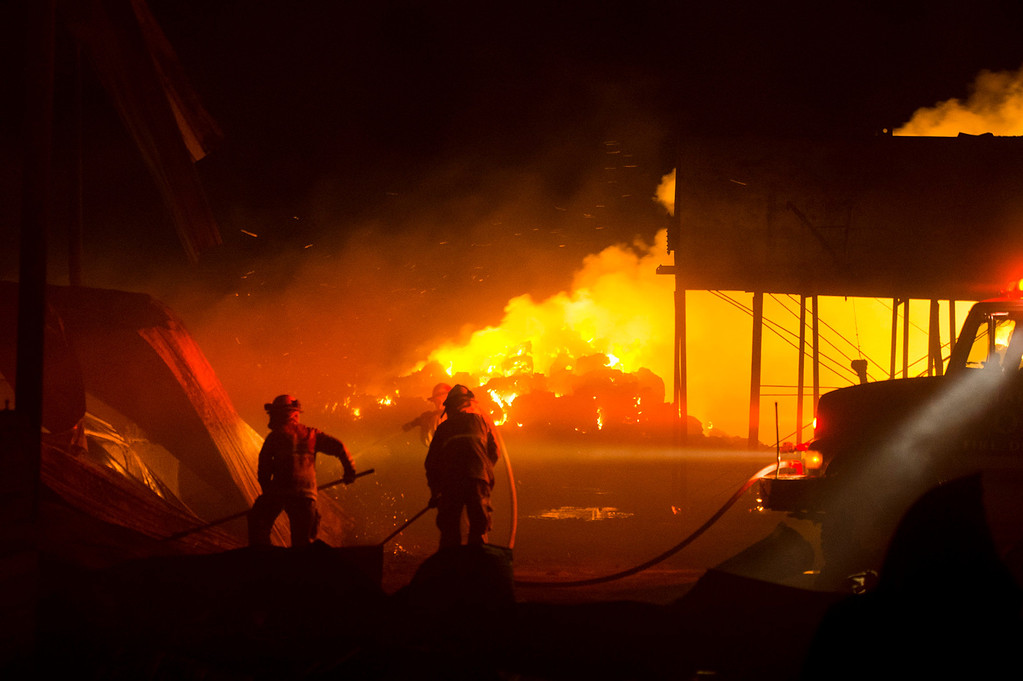 Description of . Firefighters battle a fire burning at a hay barn at Merrill Avenue and Carpenter Avenue in south Ontario on Wednesday, April 30, 2014. (Photo by Watchara Phomicinda/ San Gabriel Valley Tribune)