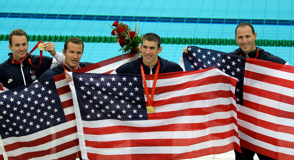 Description of . United States' Aaron Peirsol, Brendan Hansen, Michael Phelps and Jason Lezak, from left, celebrate winning the gold after the men's  4x100-meter medley relay final during the swimming competitions in the National Aquatics Center at the Beijing 2008 Olympics in Beijing, Sunday, Aug. 17, 2008.   (AP Photo/David J. Phillip)