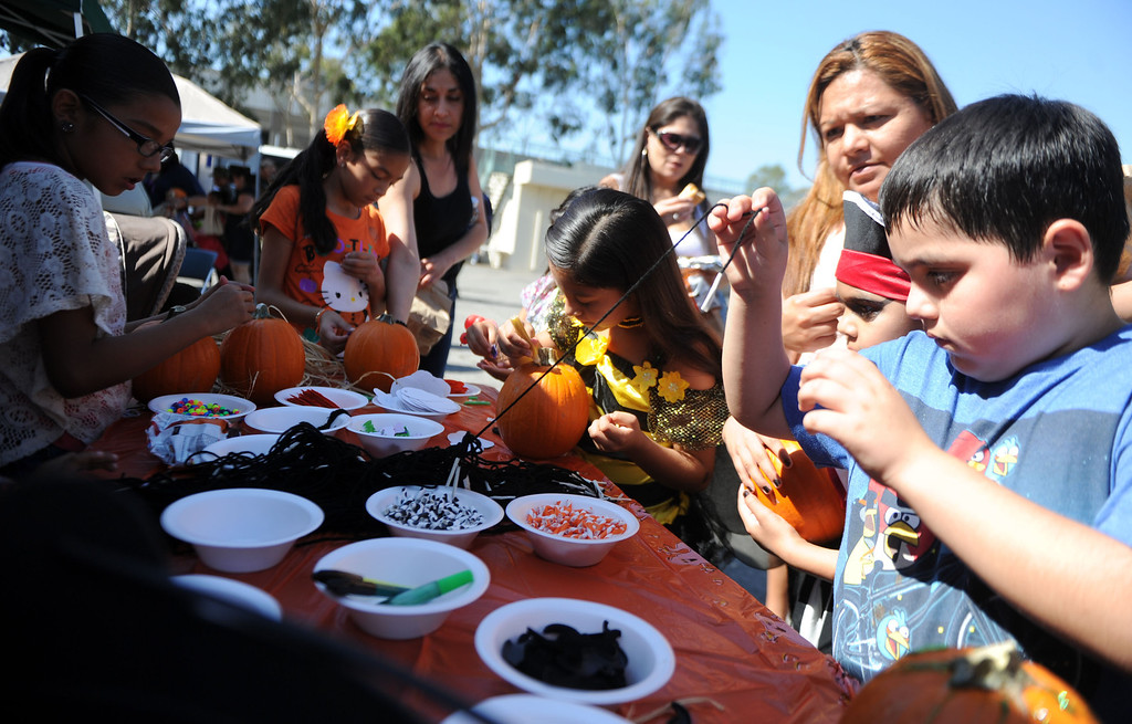 Description of . Kids and adults design pumpkins during the annual Open House and Haunted Jail at Norwalk Sheriff Station in Norwalk, Calif., on Saturday, Oct. 19, 2013. Sheriff department's Aero Bureau, SWAT, Arson Explosives Detail, Recruitment unit, along with the L.A. County Fire Department, U.S. Army with a military vehicle, CHP, and the Sheriff's Department dragster were on display.  (Keith Birmingham Pasadena Star-News)