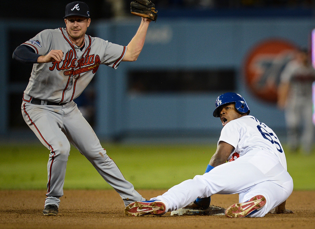 Description of . Dodgers' Yasiel Puig is out at second as Atlanta's Elliot Johnson shows the umpire the ball after making the tag during game 4 action Monday, October 7, 2013 ( Photo by Hans Gutknecht/Los Angeles Daily News )