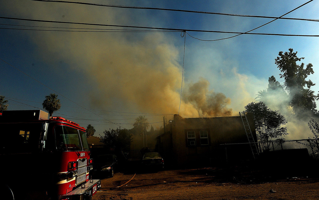 Description of . Smoke billows from a residence burned in a four-alarm fire along the 700 block of Seventh Street in San Bernardino August 18, 2013. GABRIEL LUIS ACOSTA/STAFF PHOTOGRAPHER.