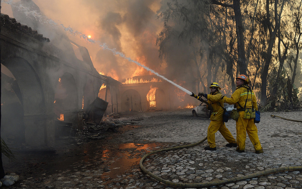 Description of . The Colby Fire burns above Glendora Thursday January 16, 2014. A portion of the former Singer home, of sewing machine fame, partially burned. (Will Lester/Inland Valley Daily Bulletin)