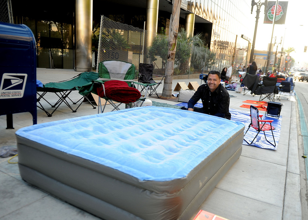 Description of . Oscar Jaime of Pasadena airs his mattress as people camp out and stake their spots for the Rose Parade along Colorado Boulevard in Pasadena, Calif., on Tuesday, Dec. 29, 2013.     (Keith Birmingham Pasadena Star-News)