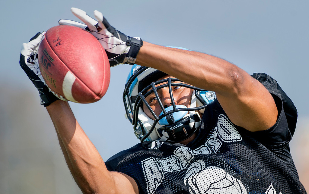 Description of . Arroyo High WR hauls in a pass during preseason practice at the El Monte campus August 14, 2013.   (SGVN/Staff photo by Leo Jarzomb)