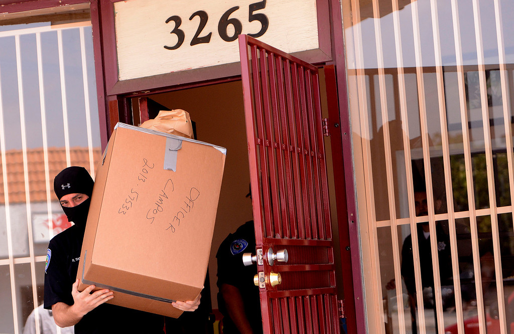 Description of . San Bernardino Police remove evidence from a marijuana dispensary along the 3200 block of North E Street in San Bernardino May 9, 2013.  (Photo by Gabriel Luis Acosta/The Sun)