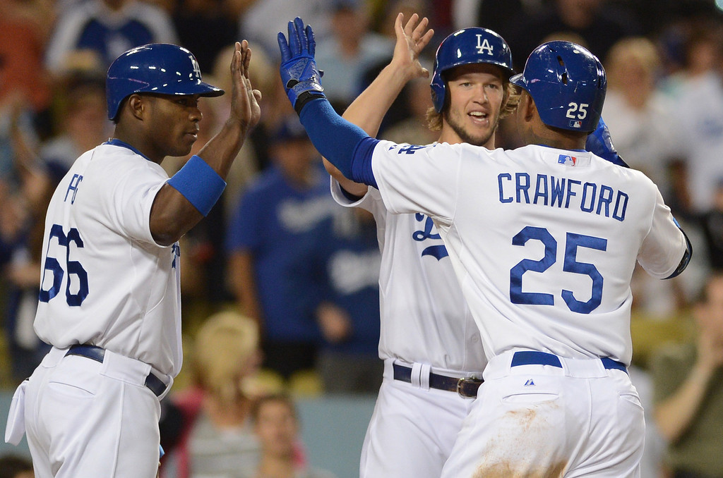 Description of . Dodgers' Yasiel Puig #66 and Clayton Kershaw #22 congratulate Carl Crawford #25 on his 3-run homer in the 4th inning during their game against the Rockies  at Dodgers Stadium Friday, September 27, 2013. Dodgers won 11-0. (Photo by Hans Gutknecht/Los Angeles Daily News)
