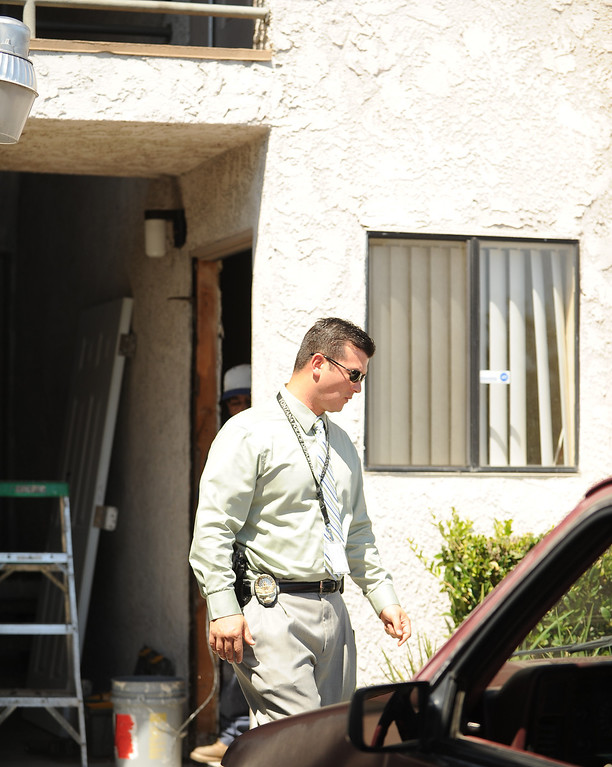 Description of . Fontana Police Detective R. Curtis walks past the apartment Wednesday, where resident Domonique Newburn, 31, was found dead, in the 7900 block of Bennett Avenue around 4:30 p.m. Tuesday while police were investigating a report of a disturbance. (LaFonzo Carter/ Staff Photographer)