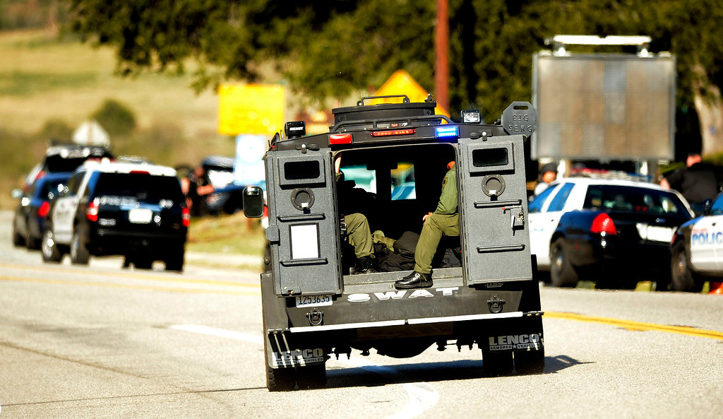Description of . A SWAT team enters a blockade at Highway 38 and Bryant Street near the Mill Street Ranger Station west of Yucaipa February 12, 2013.   Authorities believe that they exchanged gunfire with fugitive Christopher Dorner in the Angles Oaks area of the San Bernardino National Forest.  Fish and Game officers spotted a man fitting the description of Dorner driving a white pick-up, exchanged gunfire with him.  Authorities believe Dorner is holed up in a cabin on Glass Road and Highway 38.  (Staff photo by Gabriel Luis Acosta/The Sun)