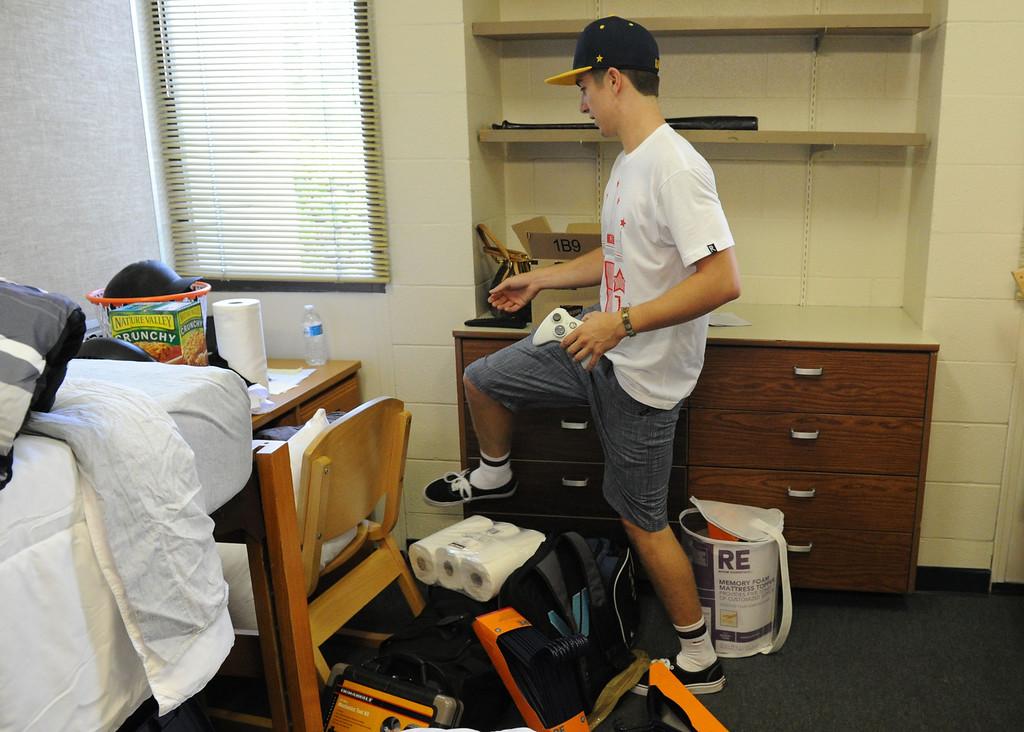 Description of . (John Valenzuela/Staff Photographer) Freshman student John White of Burbank, unpacks in his new dorm room, Wednesday morning during move-in day at the University of Redlands, August 28, 2013.