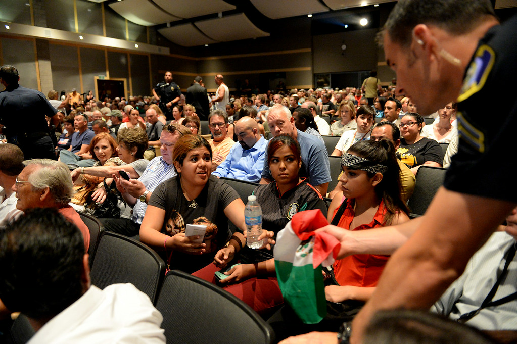 Description of . A woman has her mexican flag taken away during a town hall meeting on Wednesday, July 2, 2014 at Murrieta Mesa High School in Murrieta, Ca. No signs or flags were allowed in the meeting. The meeting is being held in response to immigrants who were being processed through a Texas Border Patrol Station and delivered to the Murrieta Border Patrol Station on Tuesday, which created protests from both sides of the immigration issue. (Micah Escamilla/The Sun)