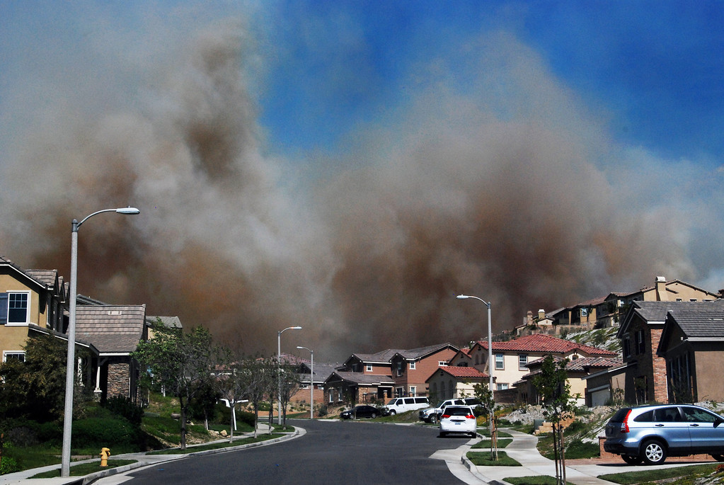 Description of . Rancho Cucamonga, Ca   Thick clouds of heavy smoke, pushed by strong Santa Ana Winds roll past a housing tract of new, million dollar homes in the hills above Rancho Cucamonga. The fire, so far, has burned through 850 acres.