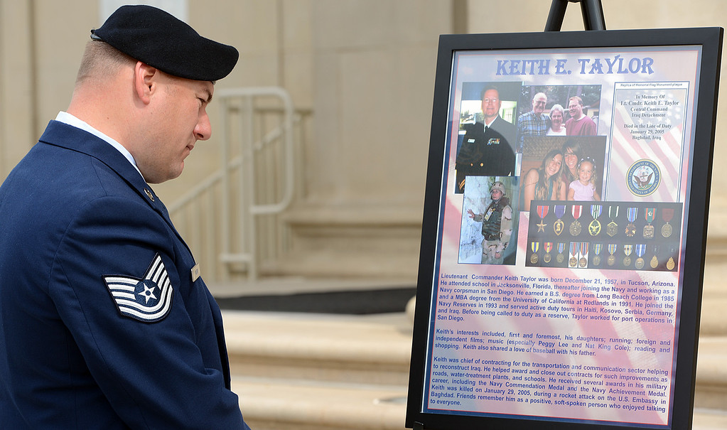 Description of . Jason Mabon, an Air Force Reservist and University of Redlands student, looks at a poster commemorating Keith Taylor during a memorial service for fallen service members Friday May 17, 2013 in front of the Memorial Chapel at the university. The ceremony featured a special tribute to Keith Taylor, a University of Redlands alumnus and father of a University of Redlands student. He was killed serving in Iraq. (Rick Sforza/Staff photographer, Redlands Daily Facts)