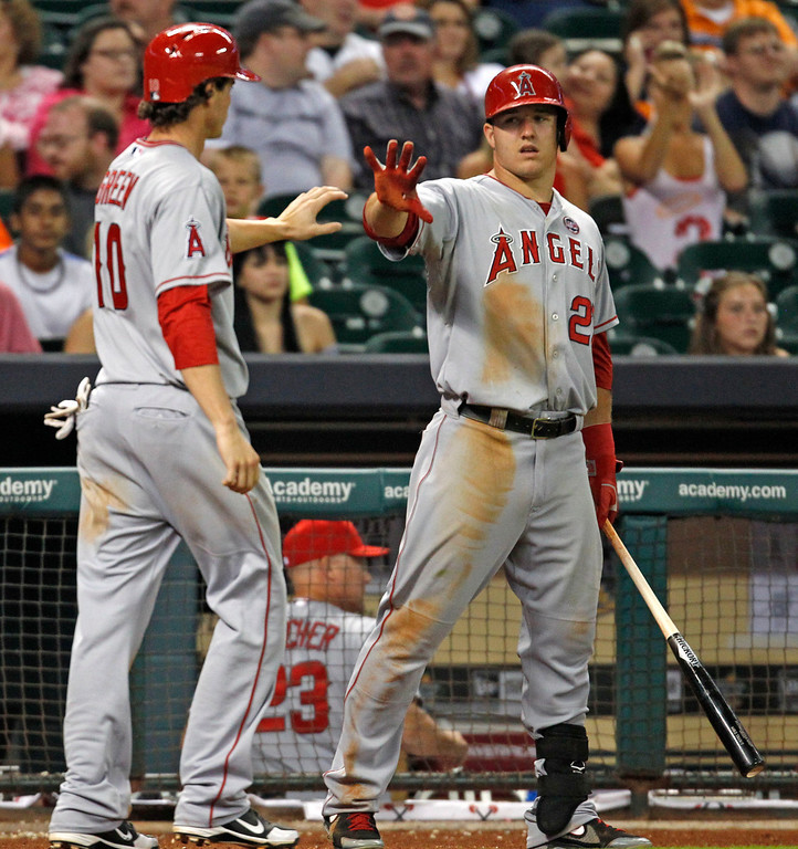 Description of . Los Angeles Angels' Grant Green, left, is congratulated by Mike Trout after scoring in the ninth inning of a baseball game against the Houston Astros on Saturday, Sept. 14, 2013, in Houston. The ANgels won 6-2. (AP Photo/Eric Christian Smith)