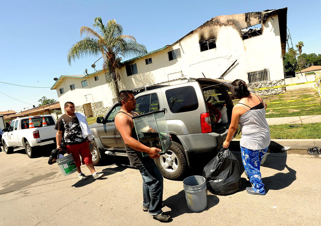 Description of . Residents remove items from their homes in the aftermath of Sunday's apartment complex fire in Highland May 13, 2013.  GABRIEL LUIS ACOSTA/STAFF PHOTOGRAPHER.