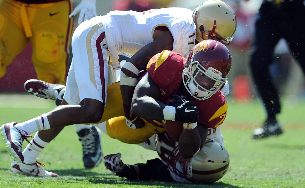 Description of . Southern California running back Tre Madden (23) dives for the first down against Boston College during the second half of an NCAA college football game in the Los Angeles Memorial Coliseum in Los Angeles, on Saturday, Sept. 14, 2013. Southern California won 35-7. 