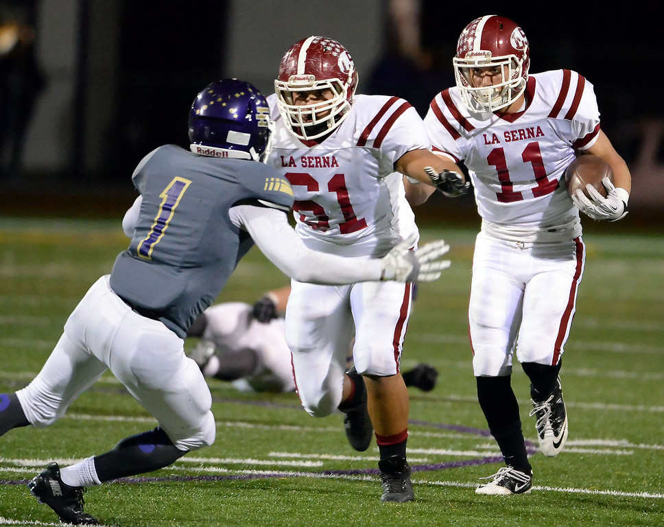 Description of . La Serna's Kevin Ramos (11) runs for yardage as Ivan Morales (61) prepares to block Diamond Bar's Tyler Brown (C) (1) in the first half of a CIF-SS playoff football game at Diamond Bar High School in Diamond Bar, Calif., on Friday, Nov. 22, 2013.   (Keith Birmingham Pasadena Star-News)