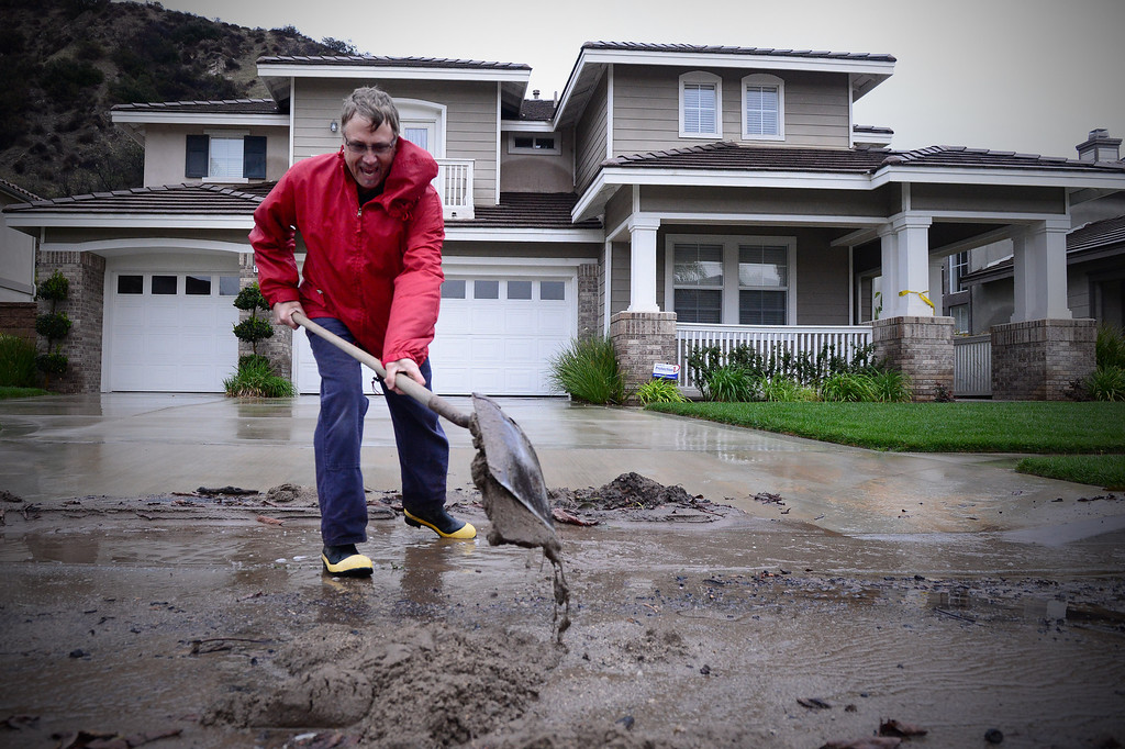 Description of . Bob Lavezzari keeps the water flowing in front of his 90 plus year old neighbor's home by shoveling sand and mud from the curb on Ridge View Drive in Azusa Saturday, March 1, 2014. The neighborhood sits below the Colby Fire burn area and one home's backyard is buried in mud. (Photo by Sarah Reingewirtz/Pasadena Star-News)