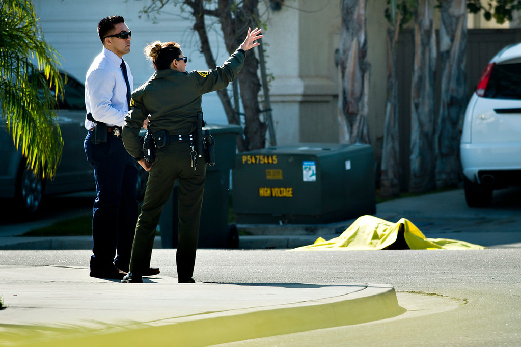 Description of . The body of a man killed by the deputies lays covered as officials investigate the scene at the 5400 block of Brushwood Court in Chino Hills on Friday, March 28, 2014. (Photo by Watchara Phomicinda/ San Gabriel Valley Tribune)