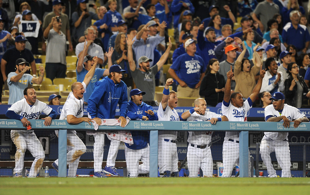 Description of . The Dodgers' bench celebrates after the Dodgers score four runs in the ninth inning to beat the Rays 7-6, Friday, August  9, 2013, at Dodger Stadium. (Michael Owen Baker/Los Angeles Daily News)