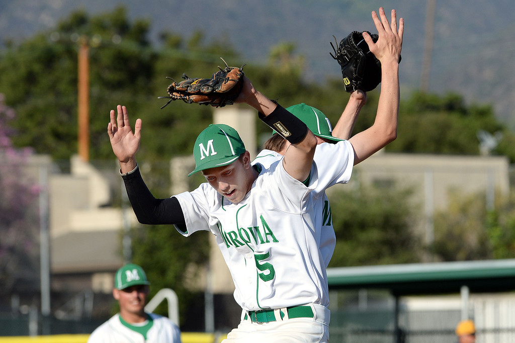 Description of . Monrovia's Nick Esparza, left, reacts with starting pitcher Brian McConnell after a complete game 2-0 one hitter over Alhambra in the first inning of the Arcadia Elk Baseball Tournament at Monrovia High School in Monrovia, Calif., on Thursday, March 13, 2014.  (Keith Birmingham Pasadena Star-News)