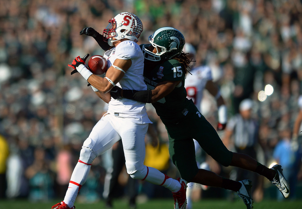 Description of . Stanford WR Michael Rector hauls in a 42-yard pass play behind Michigan State's Trae Waynes in the first quarter at the Rose Bowl, Wednesday, January 1, 2014. (Photo by Michael Owen Baker/L.A. Daily News)