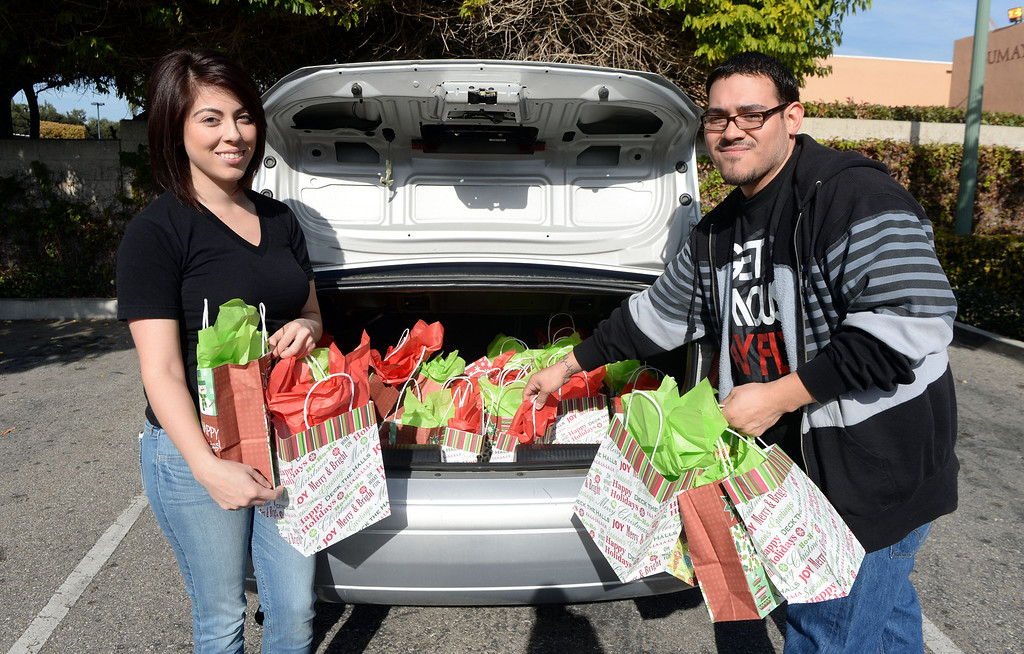 Description of . Jessica Zuniga, left, with her brother Rocky Roque of Whittier prepare to hand-out gift bags to homeless at the Whittier transportation Center in Whittier, Calif., on Saturday, Jan.4, 2014. Zuniga was given a large sum of money by an unidentified man at Target when he thought she had no money.   (Keith Birmingham Pasadena Star-News)