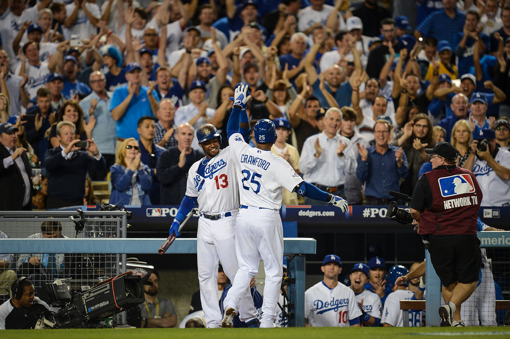 Description of . Dodgers' Carl Crawford is congratulated by Hanley Ramirez after hitting a homer at his first at bat in game 4 against Atlanta  Monday, October 7, 2013 ( Photo by Hans Gutknecht/Los Angeles Daily News )