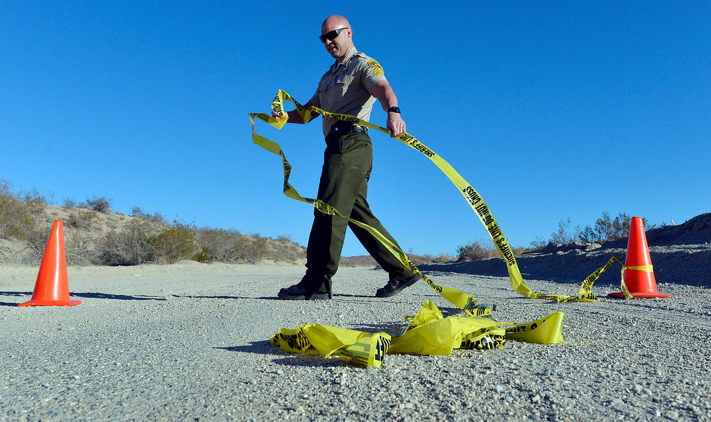 Description of . A San Bernardino County Sheriff deputy puts up crime scene tape on Quarry Road in the desert north of Victorville Wednesday morning November 13, 2013 after multiple skelton remains were found. The investigation is on going.   (Will Lester/Inland Valley Daily Bulletin)