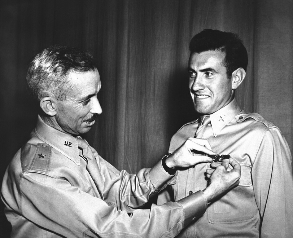 Description of . Brig. Gen. Isaiah Davics, commanding general at Midland, Tex., Army Flying School, pins a pair of silver bombardier wings Lieutenant Lou Zamperini on August 14, 1942. In 1936 Zamperini, international track star, while in Berlin for the Olympic Games as Uncle Sam's ace miler, yanked down a Nazi swastika right in front of Hilter's Palace. (AP Photo)