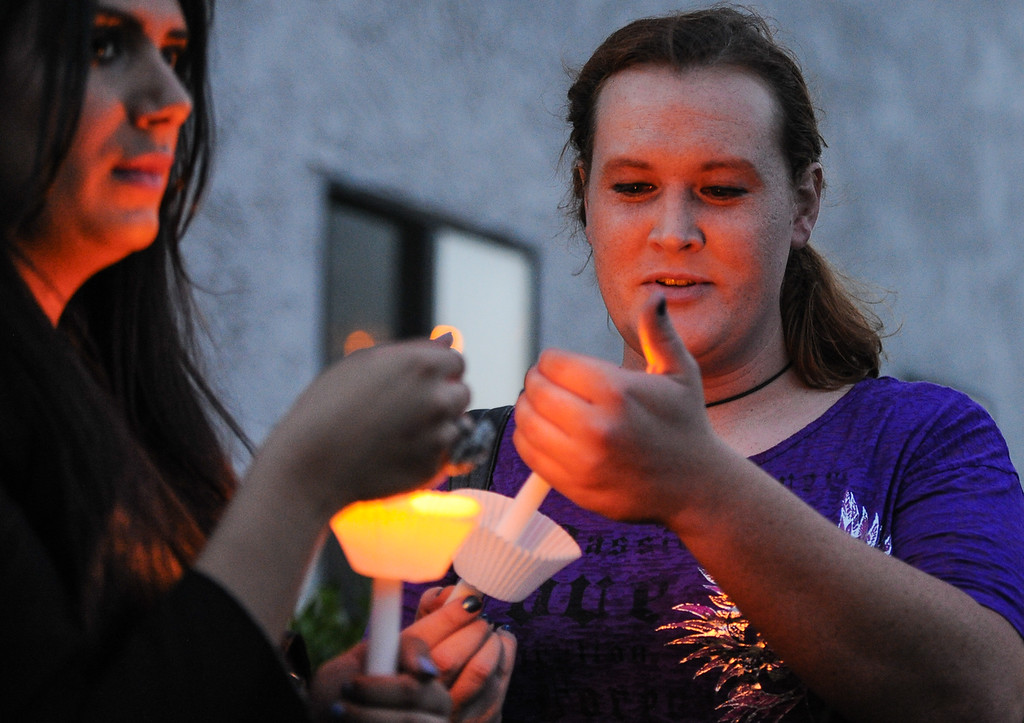 Description of . Isabel Ramirez, 23, of Riverside, left, and Tara Wallace, 26, of Moreno Valley, light candles to honor murder victim Domonique Newburn, a Fontana transgender who was found dead on Tuesday, as friends and LGBT supporters hold a candlelight vigil outside of Newburn's residence in Fontana on Wednesday, Aug. 21, 2013. Police have not made an arrest in the case, but say a man seen leaving Newburn's home in a Mercedes may be the suspect in the killing. The vehicle, which was found at Perris Hill Park Wednesday in San Bernardino, is believed to belong to Newburn. (Rachel Luna / Staff Photographer)