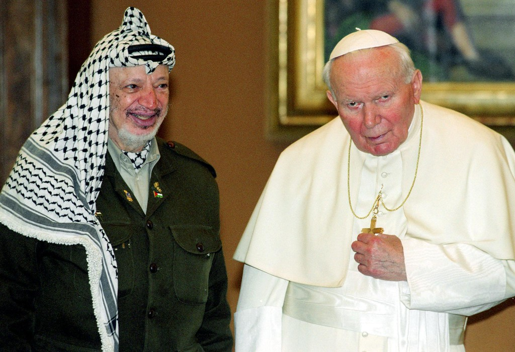 Description of . Palestinian leader Yasser Arafat presents Pope John Paul II with a nativity scene and a representation of the Last Supper, on top,  prior to their talks at the Vatican 15 February 2000.   (AFP/Getty Images)