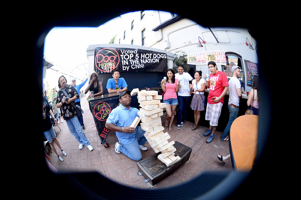 Description of . Retired Navy Commander Jerald Lacy, of Pasadena, plays a life size Jenga at Dog Haus Biergarten in Old Pasadena Saturday, July 6, 2013 before they held their First Annual Hot Dog Eating Competition.  (SGVN/Staff Photo by Sarah Reingewirtz)