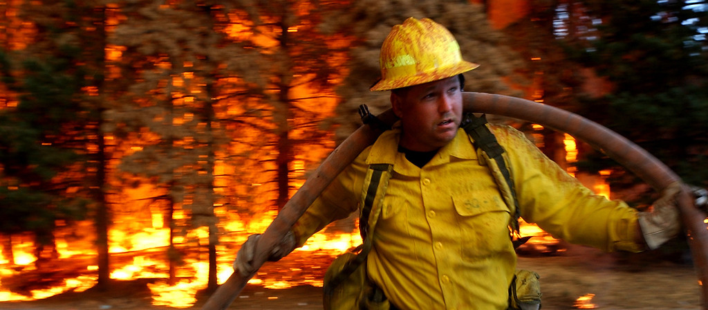 Description of . Ten years ago this month the arson caused Old Fire, fanned by Santa Ana winds burned thousands of acres, destroyed hundreds of homes and caused six deaths. The fire burned homes in San Bernardino, Highland, Cedar Glen, Crestline, Running Springs and Lake Arrowhead and forced the evacuation of thousand of residents. A Bullhead City, Arizona firefighter pulls hose away from approaching flames during the