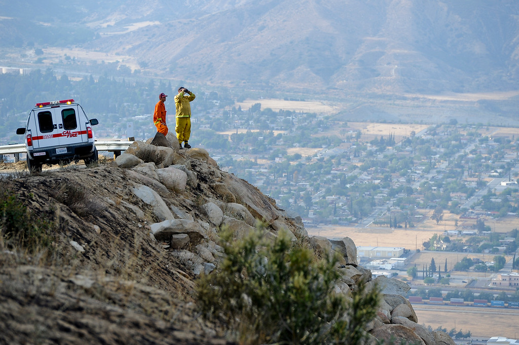 Description of . Cal Fire personnel look out to the brush fire area along Highway 243 south of Banning on Saturday, May 4, 2013. More than 400 firefighters battled the 650-acre fire on Saturday. (Rachel Luna / Staff Photographer)