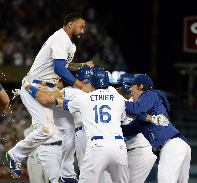 Description of . Los Angeles Dodgers' A.J. Ellis is mobbed by teammates after a game winning sac fly ball as Adrian Gonzalez (not pictured) scores the winning run in the ninth inning as the Los Angeles Dodgers defeat the San Diego Padres 1-0 during a Major league baseball game on Saturday, July 12, 2014 in Los Angeles.   (Keith Birmingham/Pasadena Star-News)